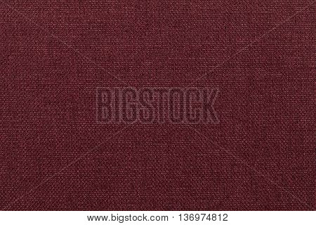 Dark red wine background from a textile material. Fabric with natural texture. Cloth backdrop.