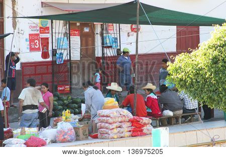 Magdalena Cajamarca Peru - July 3 2016: People eat breakfast at tables set among market goods at the Sunday market in Magdalena Cajamarca Peru on July 3 2016
