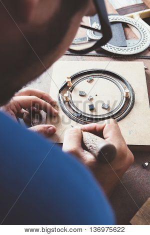 Close-up of unrecognizable man with awl making a guitar rosette at desk