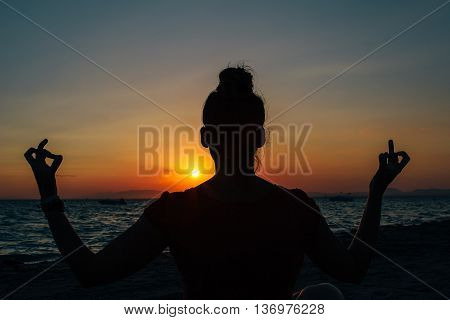 Back view of unrecognizable female meditating on beach at sunset against of sea. Backlit