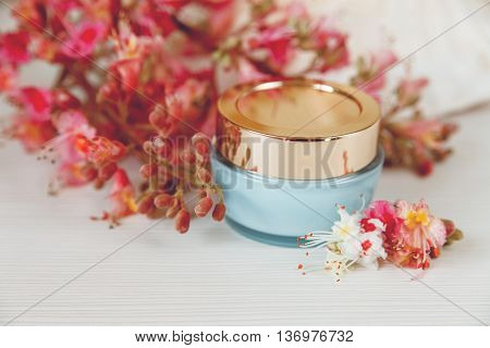 There White and Pink  Branches of Chestnut Tree with Blue and Golden Jar of Cream are on White Table,Selective Focus