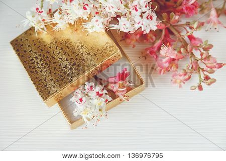 There Gold Box with White and Pink  Branches of Chestnut Tree are on White Table,Top View