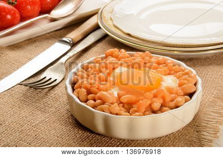 baked beans with fried egg in a round small serving plate