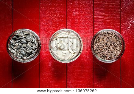 Sunflower pumpkin and linseed seeds. Healthy food in glass jars on a red wooden table.