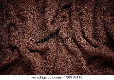 Furry wrinkled blanket texture. Close-up of brown material may be used as background.