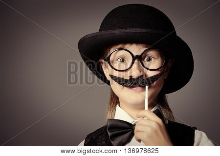 Funny boy in a bowler hat and spectacles plays with false mustache. Generation concept. Children fashion.