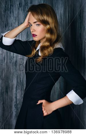 Fashion shot. Attractive young woman in classic black dress over dark background. Retro style.