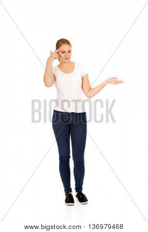 Young woman holding something on open palm and thinking about something