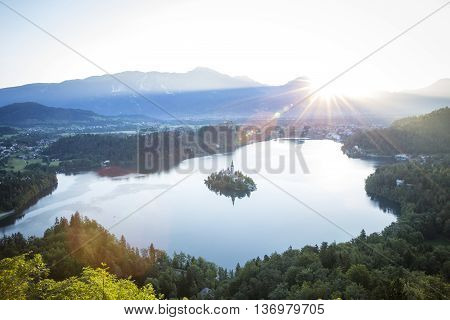 Bird view on Bled lake its island with church and the castle on a rock with Julian Alps in the background.