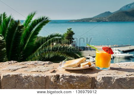 Right a glass of orange juice and toast with ham and cheese on the background of the palm branches sea and the sea berth. Breakfast of orange juice and toast with sea views. Horizontal. Daylight.