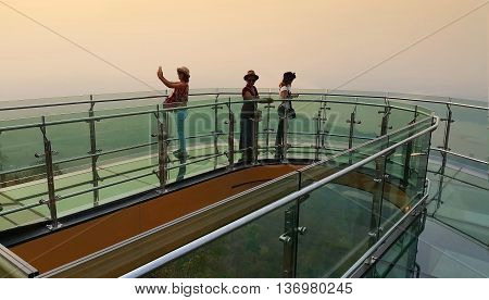 Nong Khai province Thailand- April 28 2016: Tourists walking and Selfie on transparent sky walk to see view of Mekong River during sunset at Wat Pha Tak Suea Sangkhom district Nong Khai province Thailand.