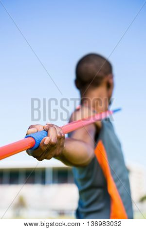 Close-up of athlete about to throw a javelin in the stadium