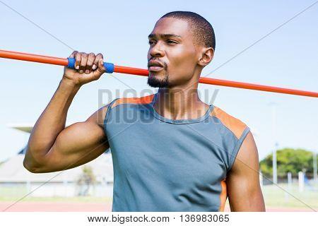 Athlete holding javelin in stadium on a sunny day