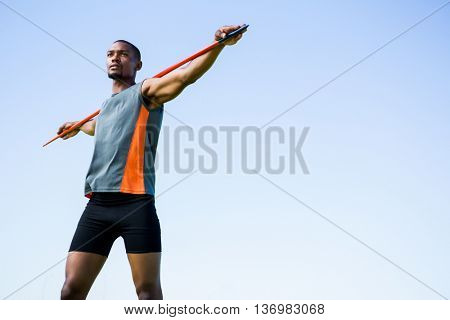 Athlete carrying javelin on his shoulder and standing in stadium