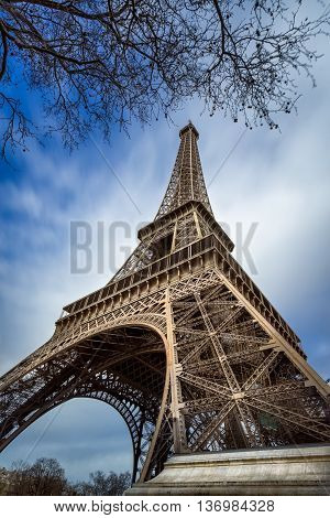 Low angle view Eiffel Tower and passing clouds, Paris, France