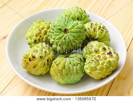 custard apple fruit on white plate with wood background