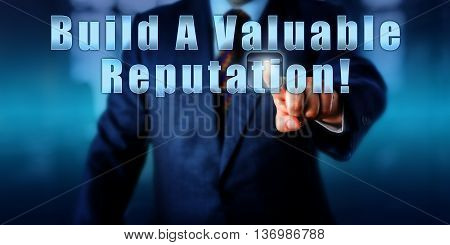Business manager is touching Build A Valuable Reputation! on a visual control screen. Motivational appeal call to action business vision concept and career development metaphor. Torso in blue suit.