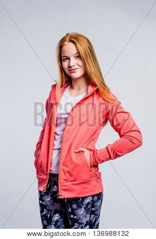 Teenage girl in red sweatshirt and fitness leggings, hands in pockets, young woman, studio shot on gray background