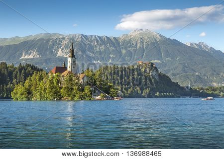 Old church on an island on Bled lake with castle on rock in the background Slovenia