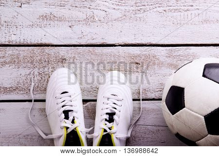 Soccer ball, cleats against wooden floor, studio shot on white background. Flat lay, copy space