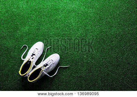 White cleats against artificial turf, studio shot on green background. Flat lay, copy space.
