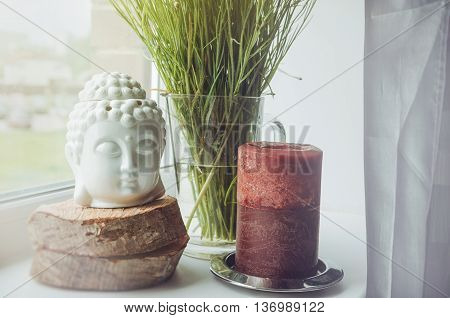 White buddha head figurine on wooden stand with big brown candle on a white windowsill green floral plant background. Home object decor in interior. Place for text free copy space.