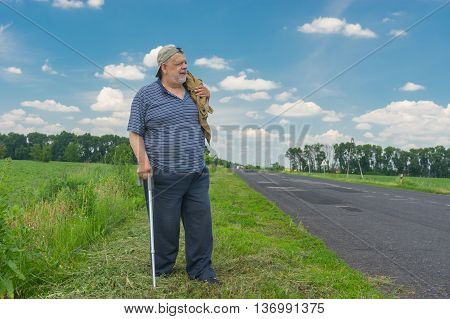 Senior man with walking stick standing on a roadside