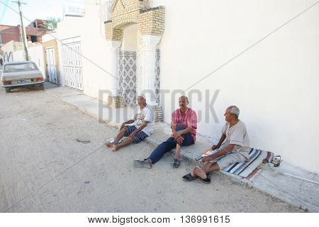 TOZEUR TUNISIA - SEPTEMBER 16 2012 : Three tunisian men sitting on the pavement in front of the house in Tozeur Tunisia.