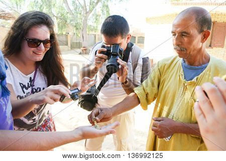 TOZEUR TUNISIA - SEPTEMBER 16 2012 : Tourists in a zoo photographing the worker putting a scorpion in a tourist hand in Tozeur Tunisia.