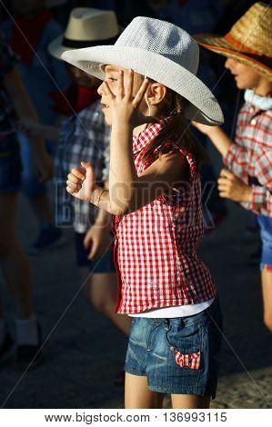 Montenegro, Herceg Novi - 04/06/2016: Children dressed as cowboys, show a cheerful dance. 10 International Children's Carnival