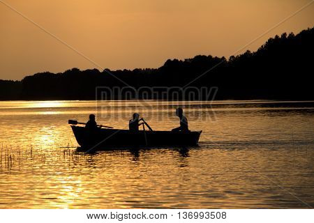 rowing wooden boat on lake in late evening with two girls and father