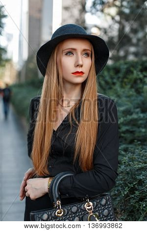 Beautiful Stylish Girl In A Hat Standing Near Green Bushes.