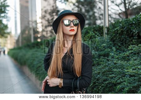 Beautiful Young Girl In A Fashionable Hat And Sunglasses Standing Near Green Bushes.