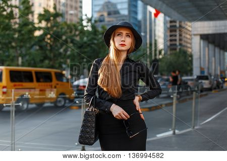 Beautiful Young Girl In A Black Hat And Stylish Strict Dress On A Background Of A Modern City.