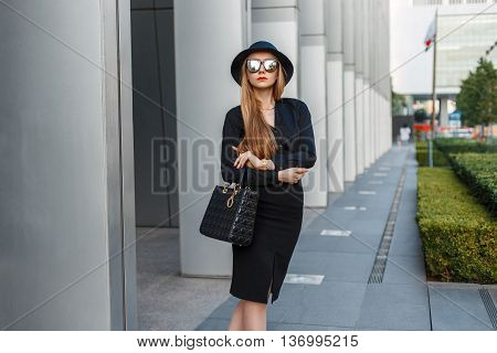 Young Beautiful Business Woman In Sunglasses And Hat Standing Near The Modern Building.