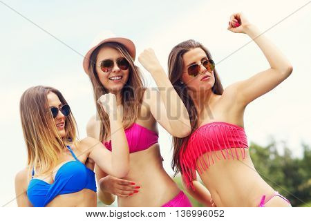 Picture presenting group of women in bikini showing muscles outdoors