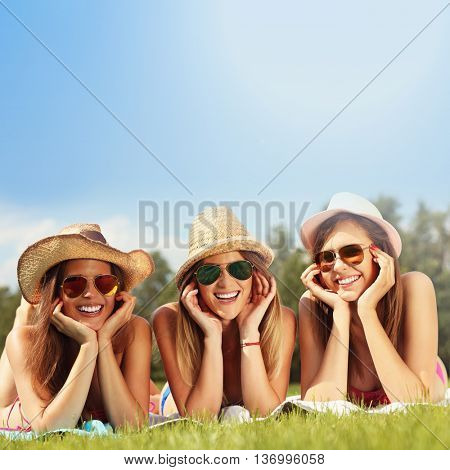 Picture showing happy group of friends lying on the grass and sunbathing