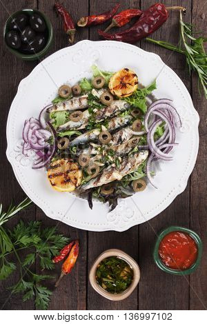 Grilled sardine fish with lemon, olives and onion