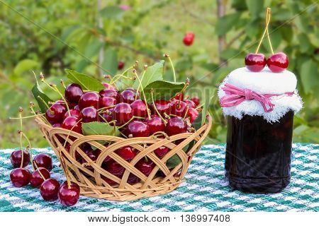 Basket of cherries and cherry jam jar on background of cherry tree