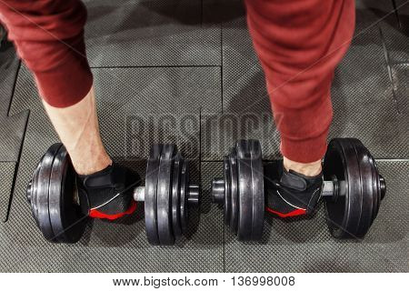 Athlete taking dumbbells from floor, athlete pov. Top view on bodybuilders arms in sportswear holding two dumbbells on gym floor. Weightlifting training closeup