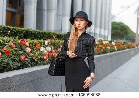 Modern Business Woman In A Stylish Clothes Walking Near The Building With Flowers.