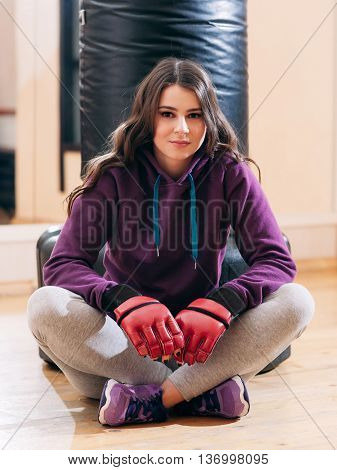 Photo of beautiful female kickboxer, having break in training. Young sporty woman in sportsuit and red boxing gloves, sitting on flor near punching bag in lotus pose, looking at photographer