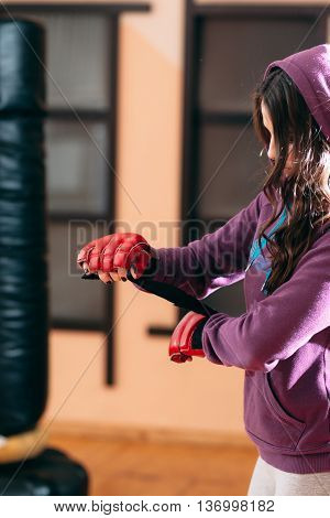 Young sportswoman wrapping hands near punching bag. Sporty girl in sport wear at gym wrapping her hands with red boxing wraps. Ready for exercises or training with punching bag female kickboxer