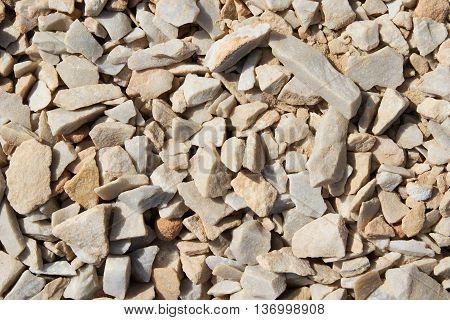 Texture yellow crushed granite sand in sunlight