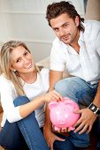 foto of save money  - Couple saving money in a piggy bank - JPG