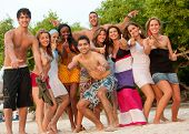 stock photo of spring break  - Happy group of friends at the beach - JPG