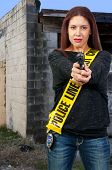 picture of crossed pistols  - A young and beautiful woman holding a handgun wearing police line tape as a sash - JPG