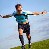 picture of open arms  - Footballer running on the field celebrating a goal - JPG