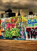 The empire state building in the background towers over a colourful wall of graffiti