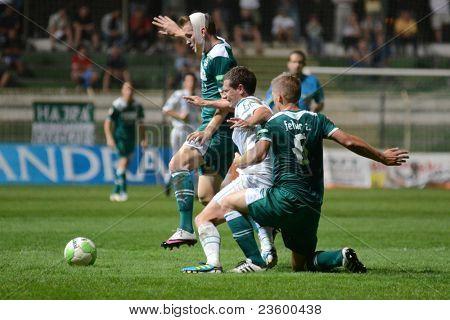 KAPOSVAR, HUNGARY - SEPTEMBER 10: Milan Peric (white 3) in action at a Hungarian National Championship soccer game - Kaposvar (white) vs Gyor (green) on September 10, 2011 in Kaposvar, Hungary.